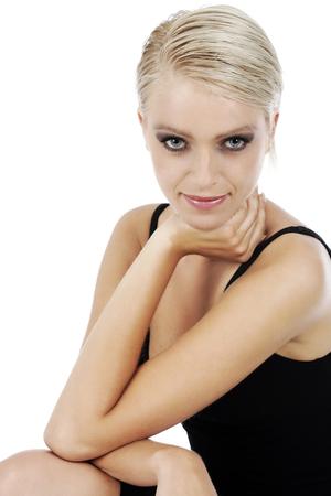 enigmatic: Elegante giovane donna bionda in un semplice abito elegante seduta schiena guardando la fotocamera con un sorriso enigmatico isolato su bianco