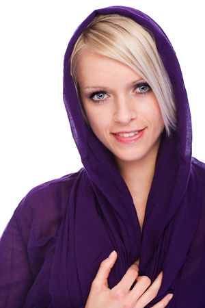 Beautiful relaxed young blond woman in a hooded purple top smiling at the camera, head and shoulders portrait on white