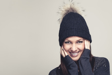 pompom: Friendly smiling young woman in winter fashion wearing a black knitted beanie with a fun furry pompom holding her hands to her ears, isolated on grey Stock Photo