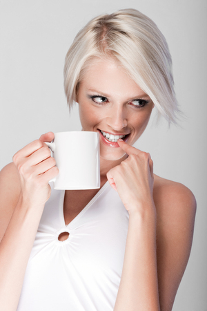 Mischievous attractive young blond woman with a short modern hairstyle standing drinking coffee and looking off to the side with a contemplative playful expression