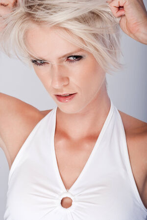 vengeful: Vindictive angry young blond woman squinting at the camera with slit eyes and a baleful expression as she tears at her hair with her hands, closeup on grey Stock Photo