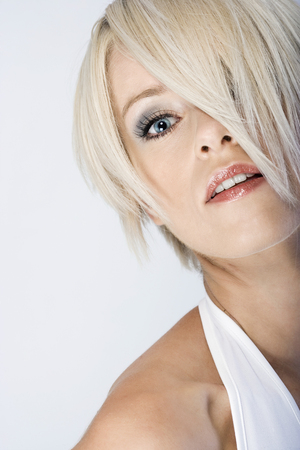 obscuring: Sexy blond woman with her short modern hairstyle obscuring one eye peering at the camera with parted lips and an intense expression Stock Photo