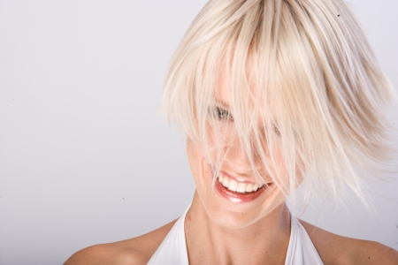 flicking: Vivacious young woman with a trendy blond hairstyle flicking her short hair in the air as she laughs at the camera Stock Photo