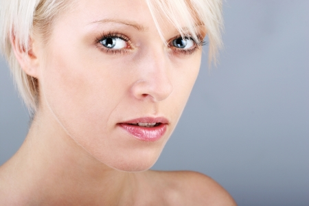 Beautiful blond with a questioning expression looking intently at the camera with parted lips, closeup facial portrait photo
