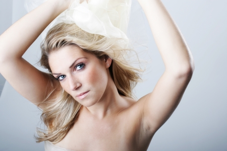 tantalising: Beautiful graceful blond woman with her arms raised in the air and long hair tossed over her bare shoulder looking at the camera with a serious expression, studio head and shoulders portrait on grey