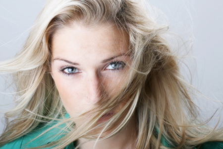speculative: Beautiful blond woman with her long hair blowing across her face giving the camera an assessing speculative look