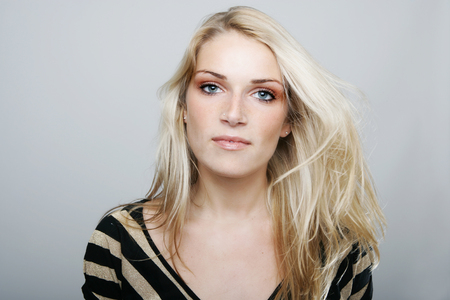 sincere: Beautiful blond woman with a sincere gentle expression full of empathy looking directly at the camera, studio head and shoulders on grey