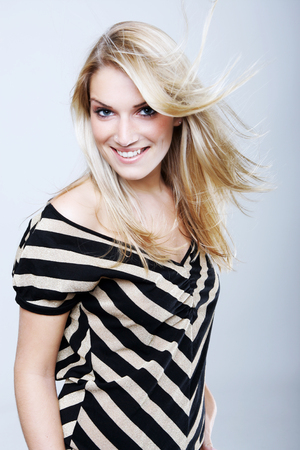 vivacious: Beautiful vivacious blond woman with a lovely friendly smile and her long hair blowing in the breeze wearing a stylish striped black and white top