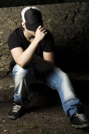 Depressed teenage sitting thinking in the late evening light with his baseball cap pulled low over his eyes Stock Photo - 24370012