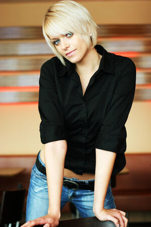Trendy slim modern young blond woman posing provocatively in tight fitting jeans and a black top with her hands resting on a table photo