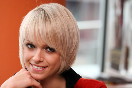 pert: Beautiful friendly young woman with trendy blond hair resting her chin on her hand smiling at the camera, closeup face portrait