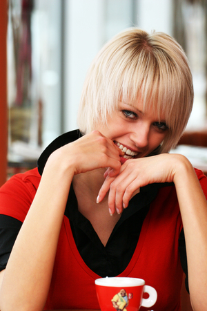 coy: Smiling beautiful blond woman with a short trendy hairstyle sitting enjoying a cup of coffee and giving the camera a coy smile from behind her hands