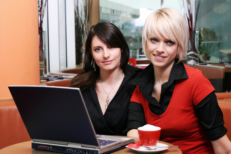 Two beautiful women friends meeting over coffee in a restaurant sit at a table together sharing a laptop computer and looking at the camera with friendly smiles photo