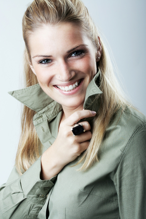 vivacious: Elegant fashionable woman with long blond hair wearing a stylish shirt and ring giving the camera a lovely vivacious charming smile Stock Photo