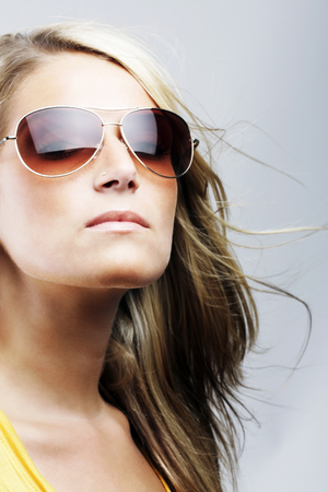 Glamorous blond woman in sunglasses with her hair blowing in the breeze staring off thoughtfully into the distance with a serious expression