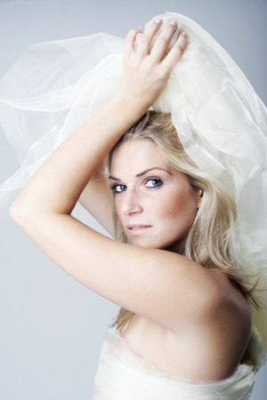 Beautiful seductive blond woman with a veil of filmy white fabric held over her head looking sideways at the camera with a serious expression photo