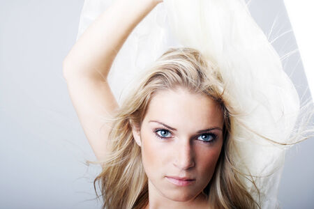 Beautiful intense young woman with long blond hair staring directly into the camera with a serious expression while holding white fabric above her head photo