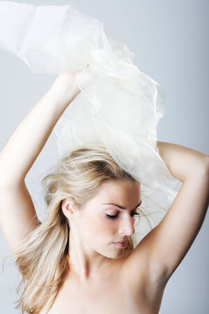 Artistic sensual portrait of a beautiful blond woman with a serene expression and downcast eyes and her arms raised holding filmy white material above her head and bare shoulders photo