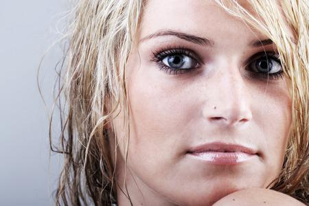 enigmatic: Bella donna bionda con i capelli umidi arruffati e lo sguardo enigmatico cupo fissando intensamente la telecamera, vista da vicino della sua faccia