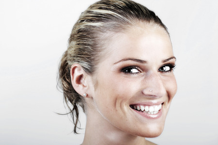 vivacious: Beautiful vivacious blond woman with wet hair looking at the camera with a beaming smile, close up face portrait on white Stock Photo