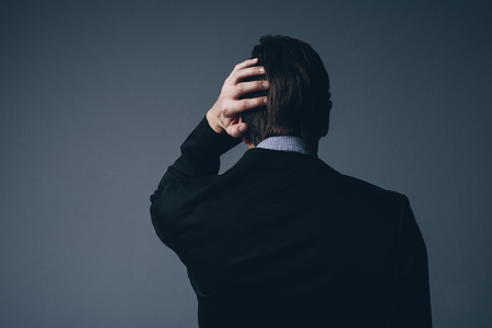 throbbing: View from behind of a stylish businessman standing with his hand to his head as he scratches it in perplexity or as he nurses a throbbing headache on a dark grey background Stock Photo
