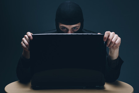 Furtive masked hacker accessing a laptop computer to steal data, plant malware or spy conceptual of cyber crime, online security and identity theft photo