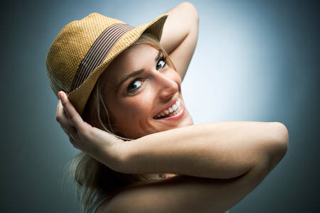 charismatic: Laughing charismatic young woman wearing a trendy straw hat turning to look back at the camera with a beautiful smile