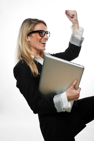 exultant: Exultant attractive blond businesswoman wearing glasses cheering and celebrating a success as she holds her laptop under her arm, side view isolated on white Stock Photo