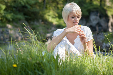 low blouse: Low angle view through green grass of a beautiful young blond woman in a white summer blouse sitting playing with meadow flowers in the sunshine Stock Photo