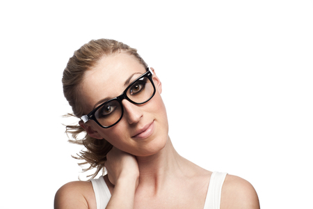 tilted: Cool portrait of a beautiful young woman in glasses with her long blond hair in a ponytail looking at the camera with her head tilted to the side and a gentle smile, isolated on white Stock Photo