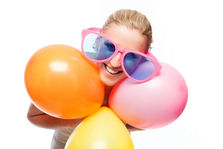 Beautiful carefree young woman enjoying a party wearing a pair of fun outsized pink glasses and holding a bunch of colorful party balloons as she celebrates, isolated on white photo