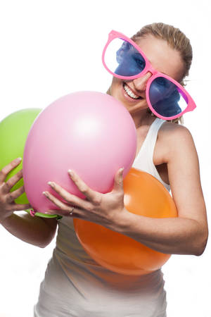 Laughing woman preparing for a party wearing a pair of funny enormous pink glasses and carrying an armful of colorful party balloons, isolated on white photo