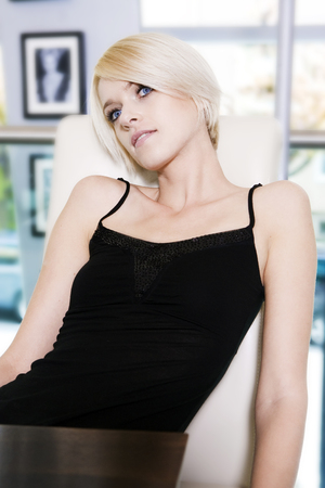 head tilted: Pretty young blond woman sitting at a table in a bright airy room filled with daylight daydreaming with her head tilted back as she stares upwards in a reverie