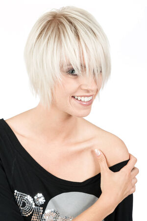 Trendy young woman with a modern blond hairstyle peeking out from under her fringe with a charming happy smile, isolated on white