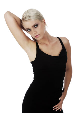 sultry: Beautiful sultry shapely blond woman posing in a black summer top with her arm raised looking at the camera with a serious expression, on white Stock Photo