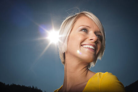 hot day: Kiss The Sun - a beautiful vivacious young blond woman has her cheek kissed by a bright sunburst as she laughs and smiles outdoors on a hot summer day against a clear blue sky, low angle view