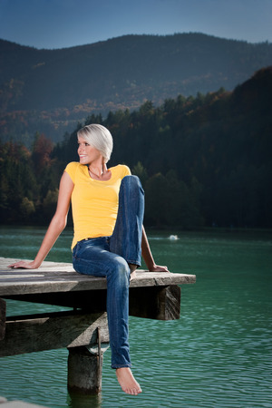 Beautiful happy slender athletic young blond woman relaxing on a lake sitting with her legs dangling off a wooden jetty against a backdrop of scenic mountains and forests