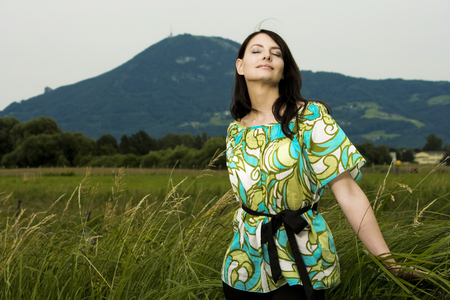 unwinding: Beautiful carefree young woman enjoying nature standing in a meadow with long grass with her head tilted back to the sun and her eyes closed in bliss , with copyspace