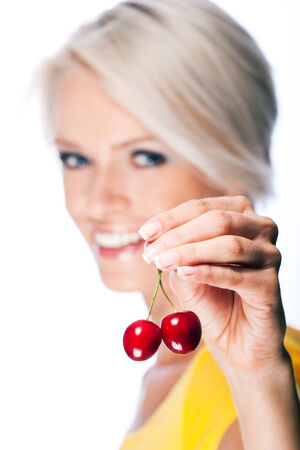 luscious: Beautiful young blond woman holding up two luscious ripe red cherries joined at the stem with focus to the cherries, isolated on white