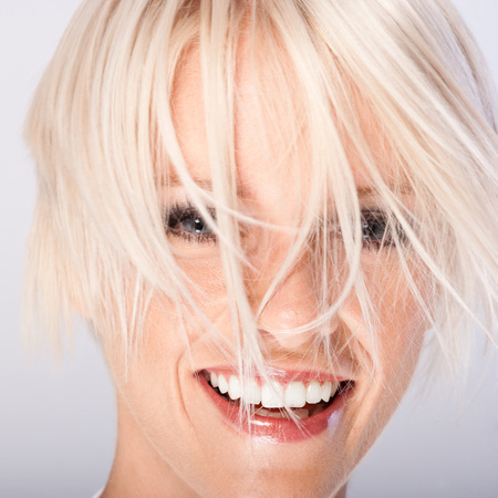 wisps: Laughing beautiful young woman with funky blond hair hanging in wisps all over her face , close up face portrait