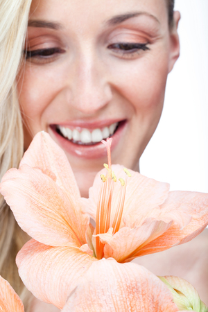 belladonna: Beautiful fresh natural ornamental orange Belladonna Lily or Amaryllis flower with the face of a gorgeous smiling blond woman in the background Stock Photo