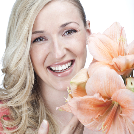Happiness and Joy - portrait of a beautiful blond woman with an expression of pure joy and happiness looking at the camera past a lovely fresh apricot colored amaryllis flower, isolated on white