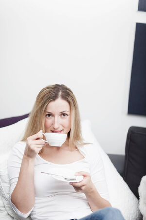 Young blond woman enjoying a cup of coffee or tea as she relaxes on a sofa in her living room while taking a break photo