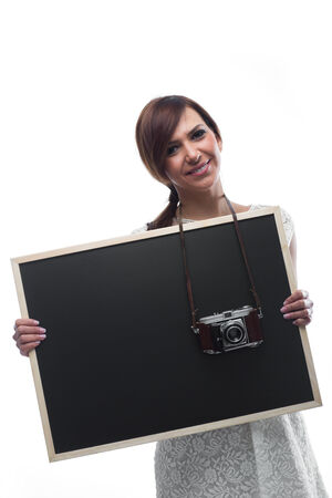 Smiling Young Woman Holding Black Board with Camera around Neck. Isolated on White Background. photo