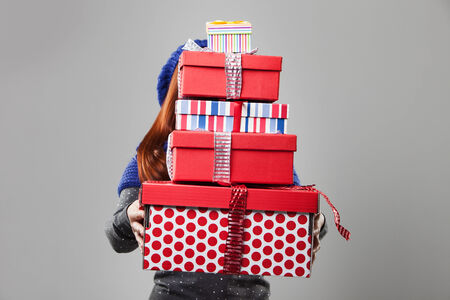 Woman Covered by Carried Gift Boxes Isolated on Gray Background. photo