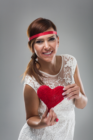 Smiling Pretty Young Woman in White Dress and Red Ribbon in Head Holding Red Heart. Isolated on Gray Background. photo