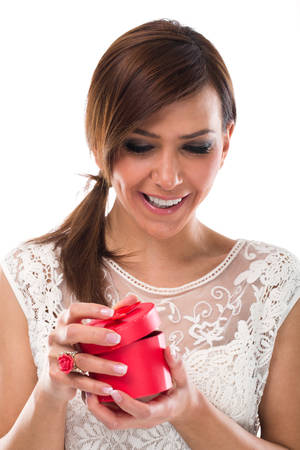 Happy Pretty Young Woman in White Lace Dress Opening Red Round Jewellery Case on White Background. photo