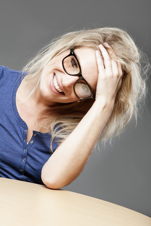 geeky: Nerdy beautiful girl with heavy rimmed glasses and tousled blond hair giving the camera a charming smile as she holds her hand to her forehead Stock Photo