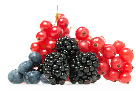 nutritive: Close-up of fresh and nutritious berries as blueberries, blackberries and redcurrants, natural source of Vitamin C and antioxidants, on white