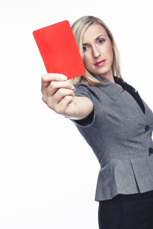 punitive: Attractive woman issuing a red card holding it up in her hand to indicate that a player is to be sent off the field, on white